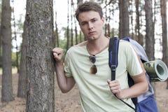 Portret van de knappe jonge mens die met rugzak in bos wandelen Royalty-vrije Stock Fotografie