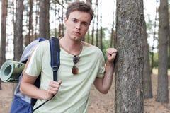 Portret van de knappe jonge mens die met rugzak in bos wandelen Stock Foto