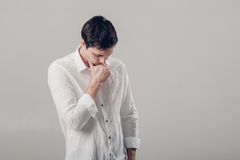 Portret van de knappe jonge peinzende mens in wit overhemd op grijze bedelaars Royalty-vrije Stock Afbeeldingen