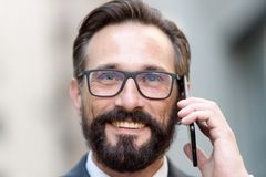 Portret van de knappe mens die en op de telefoon glimlachen spreken stock fotografie
