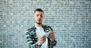 Portret van de knappe mens die van videospelletje op smartphone wat betreft het scherm genieten stock video