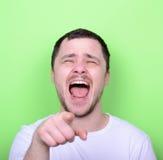 Portret van de knappe mens laughung uit luid tegen groene backgro stock afbeeldingen
