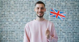 Portret van de knappe mens met Britse vlag op bakstenen muurachtergrond stock video