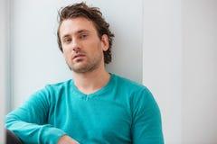 Portret van de knappe ontspannen jonge mens in blauwe verbindingsdraad Royalty-vrije Stock Afbeelding