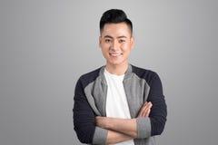 Portret van de koele knappe Aziatische mens met gekruiste wapens Stock Fotografie