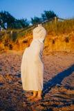 Portret van de leuke aanbiddelijke gelukkige jongen van het peutermeisje met de handdoek van het duinenstrand het verbergende beh Royalty-vrije Stock Afbeeldingen