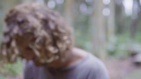 Portret van de leuke jonge mens met lang krullend haar en aap op zijn schouders stock footage