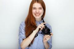 Portret van de leuke vrouw die van de roodharigefotograaf blauw gestreept overhemd dragen die met geluk en vreugde glimlachen ter Royalty-vrije Stock Foto