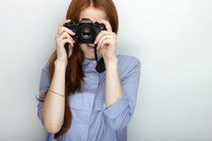 Portret van de leuke vrouw die van de roodharigefotograaf blauw gestreept overhemd dragen die met geluk en vreugde glimlachen ter Stock Afbeelding