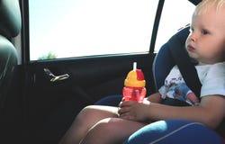 Portret van de leuke zitting van de peuterjongen in autozetel De veiligheid van het kindvervoer stock fotografie