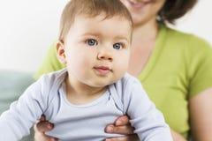 Portret van de leuke zitting van de babyjongen in zijn moederwapens. Royalty-vrije Stock Foto's