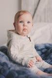 Portret van de leuke zitting van de 8 maand oude baby op het bed Royalty-vrije Stock Foto
