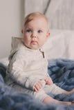 Portret van de leuke zitting van de 8 maand oude baby op het bed op gebreide deken Stock Foto
