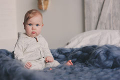 Portret van de leuke zitting van de 8 maand oude baby op het bed op gebreide deken Royalty-vrije Stock Foto's
