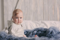 Portret van de leuke zitting van de 8 maand oude baby op het bed op gebreide deken Stock Foto's