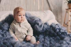 Portret van de leuke zitting van de 8 maand oude baby op het bed op gebreide deken Royalty-vrije Stock Afbeeldingen