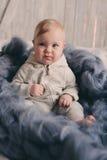 Portret van de leuke zitting van de 8 maand oude baby op het bed op gebreide deken Stock Fotografie