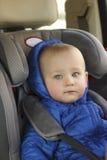 Portret van de leuke zitting van de peuterjongen in autozetel De veiligheid van het kindvervoer stock afbeeldingen