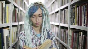 Portret van de lezingsboek van de hipstervrouw in bibliotheek stock video