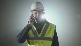 Portret van de man in de eenvormige bouwers en helm die door celtelefoon spreken voor de zwarte achtergrond met stock video
