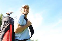 Portret van de mannelijke zak van het golfspeler dragende golf terwijl het lopen door groen gras van golfclub stock afbeeldingen