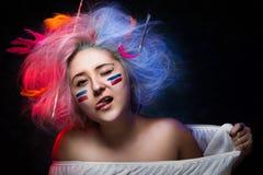 Portret van de meisjesschilder met kleurenverf op gezicht met tatoegering op hand en borstels voor tekening in het haar Stock Fotografie