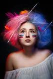 Portret van de meisjesschilder met kleurenverf op gezicht met tatoegering op hand en borstels voor tekening in het haar Stock Afbeeldingen