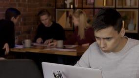 Portret van de mens achter laptop op achtergrond van rustende bezoekers aan koffie stock video