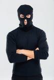 Portret van de mens in balaclava die zich met gekruiste wapens bevinden Stock Fotografie