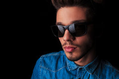 Portret van de mens in denim die zonnebril in donkere studio dragen Stock Fotografie