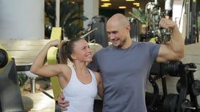 Portret van de mens en vrouw die met glimlach bicepsen op hun handen tonen stock video