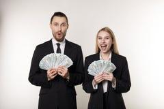 Portret van de mens en vrouw in de zwarte ventilator van de kostuumholding van dollargeld die en camera glimlachen bekijken stock afbeeldingen