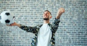 Portret van de mens met voetbal het vieren overwinning op bakstenen muurachtergrond stock footage