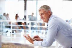 Portret van de midden oude mens in bureau die tablet gebruiken Royalty-vrije Stock Afbeelding