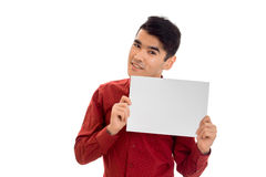 Portret van de modieuze jonge mens in rode t-shirt met leeg aanplakbiljet in zijn die handen op witte achtergrond wordt geïsoleer Royalty-vrije Stock Foto's