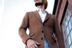 Portret van de modieuze knappe jonge mens in glazen met varkenshaar die zich in openlucht bevinden Mens die jasje en overhemd dra stock foto