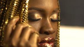 Portret van de mooie aantrekkelijke Afrikaanse vrouw met rode glanzende lippen en gouden potten, bronsoogschaduw en eyeliner stock videobeelden