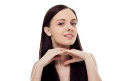 Portret van de mooie donkerbruine het glimlachen handen van de meisjesholding op haar Stock Foto's