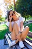 Portret van de mooie donkerbruine zomer in zonnebril die op de bank in witte blouse en denimborrels in zitten Royalty-vrije Stock Fotografie