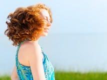 Portret van de mooie jonge vrouw met fladderend rood haar Royalty-vrije Stock Fotografie