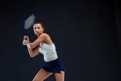 Portret van de mooie speler van het meisjestennis met een racket op donkere achtergrond Stock Fotografie