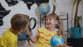 Portret van de mooie twee leerlingen die met pretstudie de bol met een vergrootglas in haar klaslokaal indient Bij stock footage