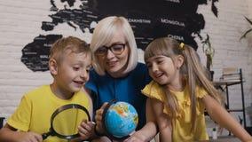 Portret van de mooie twee leerlingen en de jonge leraar die in glazen met pret de bol met een hoofdroos in haar handen bestuderen stock videobeelden