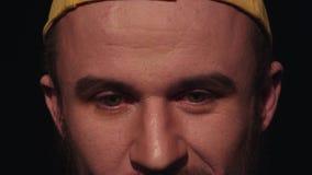 Portret van de onzekere jonge Kaukasische mens die met baard in geel GLB neer kijken stock video