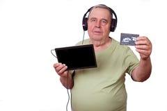Portret van de oude mens die aan muziek in oortelefoons luisteren die een tabl gebruiken stock foto