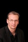 Portret van de oudere ernstige mens op zwarte Stock Foto's