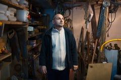 Portret van de peinzende volwassen mens in zijn workshopruimte royalty-vrije stock afbeeldingen