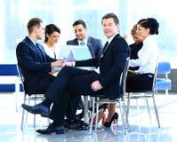 Portret van de rijpe bedrijfsmens die tijdens vergadering met collega's glimlacht Stock Foto
