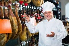Portret van de rijpe winkelmens die Spaanse jamon aanbieden Royalty-vrije Stock Foto's