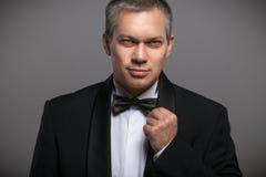 Portret van de sexy mens in zwarte kostuum en vlinderdas Stock Fotografie